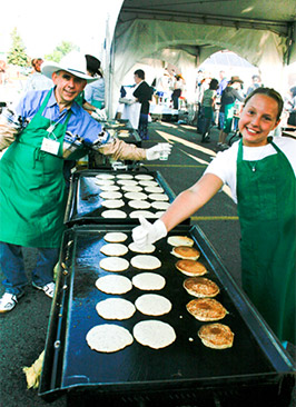 Hannah Biggs and John Couto cooking pancakes at the Community Natural Foods Stampede Breakfast in 2010